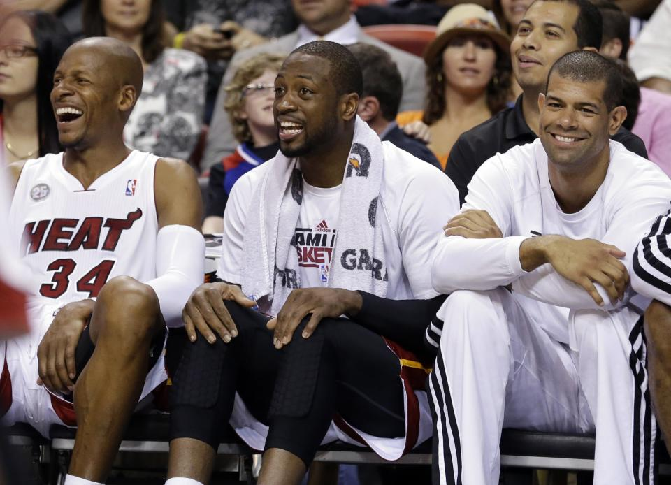 Miami Heat guard Ray Allen, left, guard Dwyane Wade, center, and forward Shane Battier, right, watch from the bench during the final seconds of an NBA basketball game against the Orlando Magic, Wednesday, April 17, 2013 in Miami. The Heat defeated the Magic 105-93. (AP Photo/Wilfredo Lee)