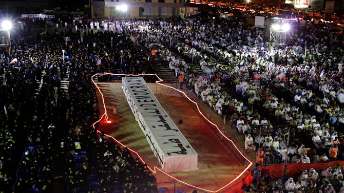 "Pro-democracy protesters listen to speakers at a rally organized by opposition groups while seated around a stage shaped like the boundaries of Bahrain and containing a mock casket with the word ""democracy"" in English and Arabic. Bahrain says it has charged seven police lieutenants with alleged abuses against suspected anti-government protesters, including using torture to obtain confessions that were later thrown out in court. (AP Photo/Hasan Jamali)"