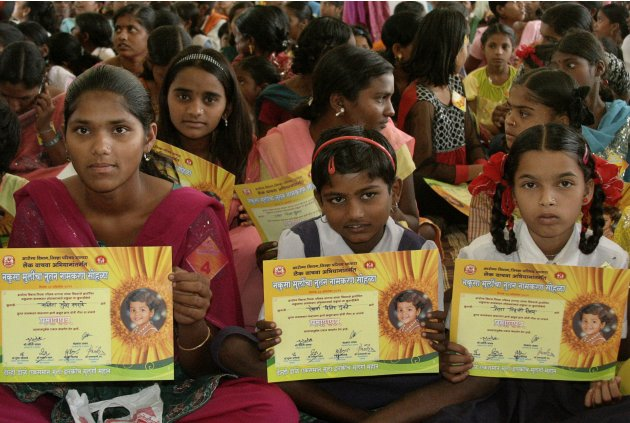 "Girls hold certificates stating their new official names during a renaming ceremony  in Satara, India, Saturday, Oct. 22, 2011. Almost 300 Indian girls known officially as ""Unwanted"" have traded their"