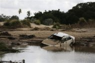 A car lies partially submerged in floodwater at the golf course of a hotel in the flooded Mexican beach resort of Acapulco September 18, 2013. REUTERS/Tomas Bravo