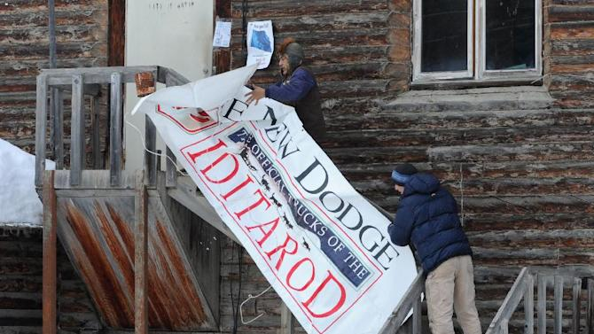 Iditarod checker Wilson Maillelle and volunteer Darren Hull put up an Iditarod banner at the checkpoint in Anvik as the Yukon RIver community anticipates the arrival of the first Iditarod mushers on Thursday, Mar. 7, 2013. The Millennium Alaskan Hotel Anchorage has flown its chef 350 miles to this remote Alaska village of 82 people to whip up a gourmet meal for the first musher to get to the first checkpoint along the 1,800-mile long Yukon River.  (AP Photo/Anchorage Daily News, Bill Roth)