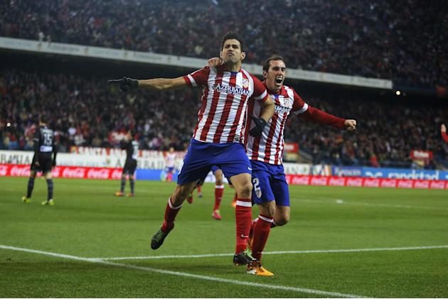 Atletico's Diego Costa, left, celebrates his goal with Diego Godin during a Spanish La Liga soccer match between Atletico de Madrid and Levante at the Vicente Calderon stadium in Madrid, Spain, Sa