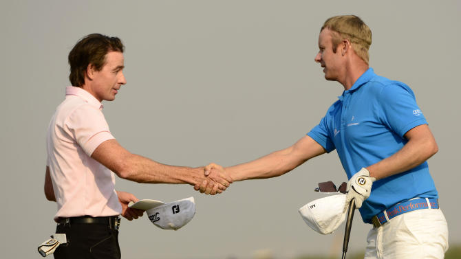 In this photo released by OneAsia, Brett Rumford of Australia, left, shakes hands with Mikko Ilonen of Finland on the 18th green during the third round of China Open golf tournament at Tianjin Binhai Lake Golf Club in Tianjin, China on Saturday, May 4, 2013. (AP Photo/OneAsia, Paul Lakatos) NO LICENSING