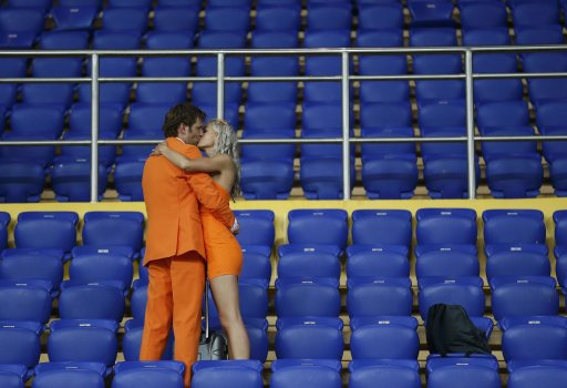 Netherlands' fans kiss at the end of their Group B Euro 2012 soccer match against Germany at the Metalist stadium in Kharkiv