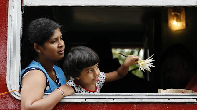 A Sri Lankan Tsunami survivor travels with her son in the 591 train which was hit by 2004 tsunami during a commemorative ride in Peraliya, Sri Lanka, Friday, Dec. 26, 2014.  In Sri Lanka the train 591, which was tossed up by the waves and the charred images of which became an icon of the disaster, carried some survivors, relatives of the dead and the guard who was on duty 10 years ago, stopped at the disaster site for a remembrance of the dead. The train including the original locomotive and five carriages was decorated with Buddhist flags and Buddhist chanting was played through the journey. (AP Photo/Eranga Jayawardena)