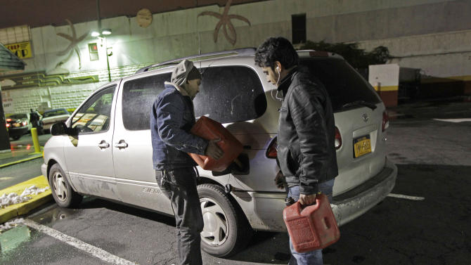 Mohammed Ismael, right, watches his friend Robbie Hassan fill his car with gasoline in Brooklyn, where gas is still scarce, Thursday, Nov. 8, 2012, in New York.  Fuel shortages and distribution delays that led to gas hoarding have prompted New York City and Long Island to initiate an even-odd gas rationing plan which begins Friday at 6 a.m. in New York and 5 a.m. in Long Island. (AP Photo/Kathy Willens)