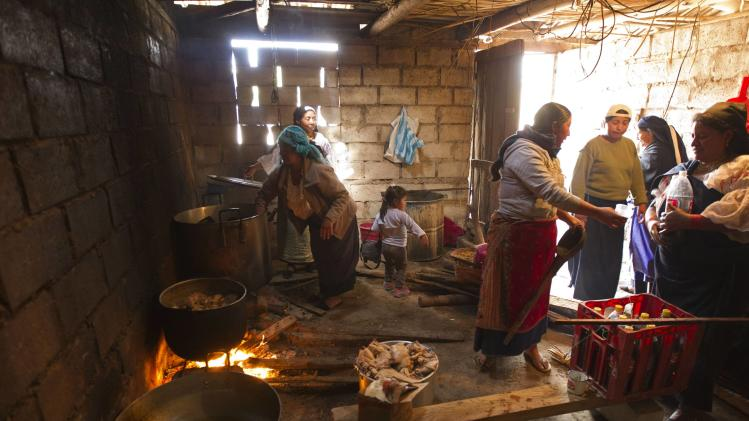 Ecuadorean indigenous indian women prepare food as men build a house in Otavalo