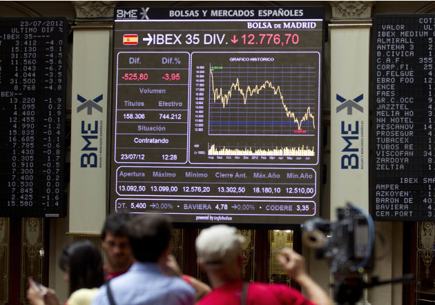 Journalists work at the Stock Exchange in Madrid Monday July 23, 2012. The Bank of Spain says the country's recession-plagued economy contracted 0.4 percent in the second quarter, a performance even w