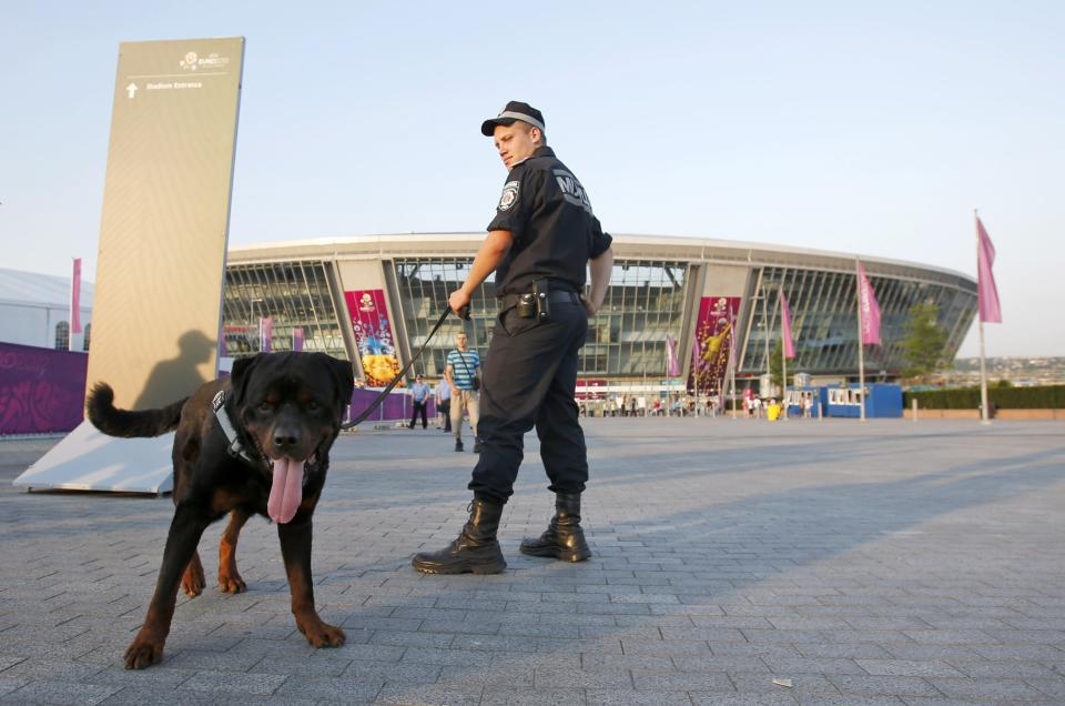 A Ukrainian police officer patrols with a sniffer dog before the start of the Euro 2012 soccer championship quarterfinal match between Spain and France in Donetsk, Ukraine, Saturday, June 23, 2012. (AP Photo/Darko Vojinovic)