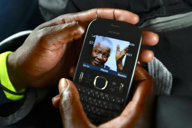 A public taxi passenger displays his cellphone wallpaper showing a picture of former South African President Mandela in Johannesburg
