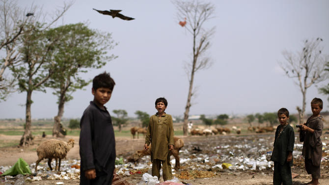 In this Friday, Aug. 10, 2012 photo, an Afghan refugee boy, center, shouts at another boy, not pictured, while he and others search for useful items in a pile of garbage next to a slum area on the outskirts of Islamabad, Pakistan. Hundreds of thousands of Afghan refugees are in limbo as Pakistan, increasingly frustrated with hosting the world's largest and longest-running refugee population, weighs whether to renew their refugee status by the end of this year. A large-scale return of the 1.7 million Afghan refugees currently living in Pakistan would be a massive problem for Afghanistan at a time when it's already struggling to maintain security in the face of an American troop withdrawal. But Pakistan increasingly seems to be angry at a refugee population that many feel has overstayed its welcome. (AP Photo/Muhammed Muheisen)