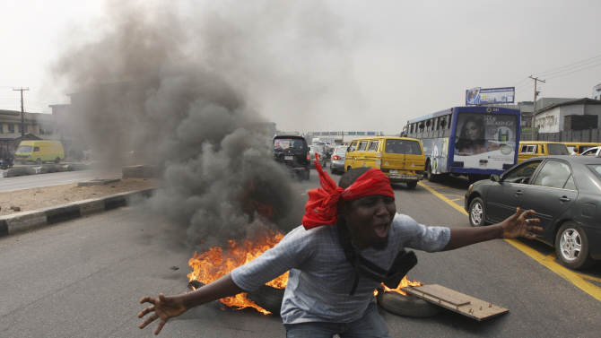 "FILE- An unidentified man shouts slogans near burning tyres during a protest on a major road junction in the commercial capital of Lagos, Nigeria, during a fuel subsidy protest in this file photo dated Tuesday, Jan. 3, 2012, as angry mobs call on the government to keep a cherished consumer subsidy that had kept gas affordable for more than two decades. A 30-minute film documentary called ""Fuelling Poverty"" has been online for months, but it is revealed Sunday April 21, 2013, that Nigerian officials have refused its director Ishaya Bako permission to show it publicly in this oil-rich nation, as it focuses on the January 2012 protests and the alleged billions of dollars thought to have been swallowed up by greedy companies and the nation's elite.(AP Photo/Sunday Alamba, FILE)"