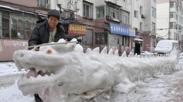 A man looks at a dragon-shaped snow sculpture made by local residents at a residential compound in Jilin