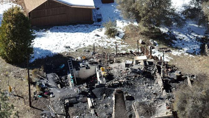 In this aerial photo, law enforcement authorities investigate the charred remains of a cabin Wednesday, Feb. 13, 2013, where quadruple-murder suspect Christopher Dorner is believed to have died after barricading himself inside during a Tuesday stand-off with police in the Angeles Oaks area of Big Bear, Calif. San Bernardino Sheriff's Deputy Jeremiah MacKay was killed and another wounded during the shootout with Dorner. (AP Photo/The Sun, John Valenzuela)