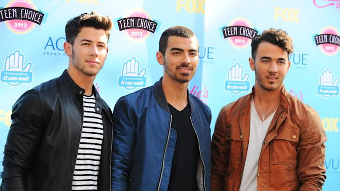 FILE - In this Aug. 11, 2013 file photo, from left, Nick Jonas, Joe Jonas and Kevin Jonas of the musical group Jonas Brothers arrive at the Teen Choice Awards at the Gibson Amphitheater, in Los Angeles. The Jonas Brothers are canceling their tour two days before it begins on Oct. 11, 2013. (Photo by Jordan Strauss/Invision/AP, File)