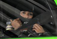Danica Patrick adjusts her gear before leaving her garage in her number 10 Chevrolet during NASCAR Sprint Cup Series practice at the Daytona International Speedway in Daytona Beach, Florida February 22, 2013. The Daytona 500 NASCAR Sprint Cup race is scheduled for February 24, with Patrick starting in the pole position. REUTERS/Brian Blanco