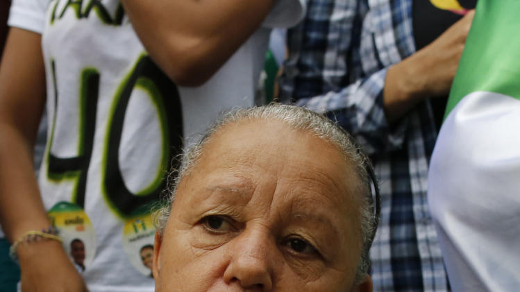 """A supporter of Marina Silva, presidential candidate of the Brazilian Socialist Party, holds a newspaper showing Silva with late candidate Eduardo Campos, who died in a plane crash in August, that reads in Portuguese """"Courage,"""" as she waits for Silvia to arrive to campaign in the Rocinha slum in Rio de Janeiro Brazil, Saturday, Aug. 30, 2014. Silva, who became the party's presidential candidate after Campos' death, is leading polls against current President Dilma Rousseff, and tapping into the widespread frustrations of many Brazilians with a sputtering economy and poor public services. Brazil will hold its presidential election on Oct. 5. (AP Photo/Leo Correa)"""