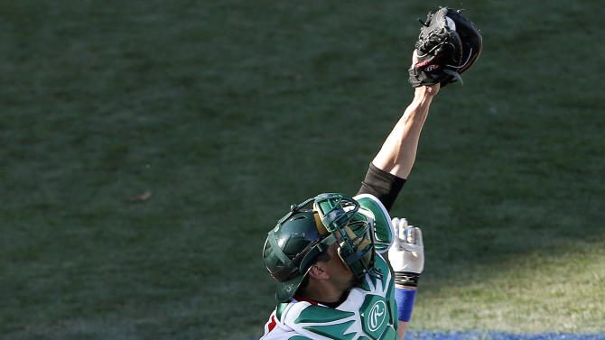 Italy's Chris DeNorfia scores the winning run as Mexico's Humberto Cota jumps for the throw in the ninth inning of a World Baseball Classic baseball game, Thursday, March 7, 2013, at Salt River Fields in Scottsdale, Ariz. Italy won 6-5. (AP Photo/Matt York)