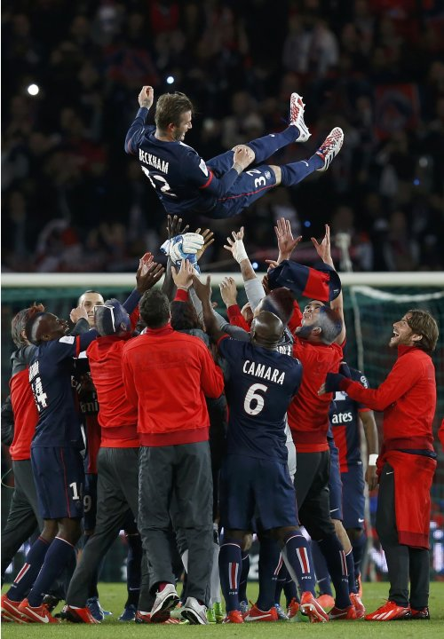 Paris Saint-Germain players throw David Beckham in the air at the end of their team's French Ligue 1 soccer match against Brest at the Parc des Princes stadium in Paris