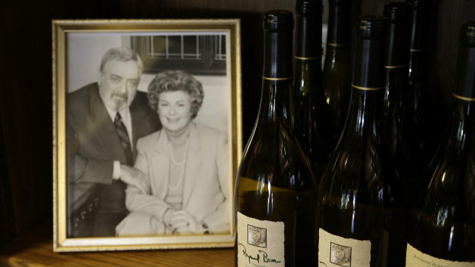 """In this photo taken Thursday, April 11, 2013 bottles of Chardonnay are shown beside of photograph of the late actor Raymond Burr and actress Barbara Hale at Raymond Burr Vineyards in Healdsburg Calif. The star of TV's """"Perry Mason"""" and """"Ironside,"""" also had a passion for wine, which is still celebrated at this small winery in Sonoma County's Dry Creek Valley. (AP Photo/Eric Risberg)"""