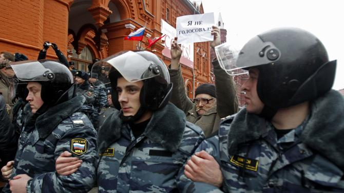 """A man holds up a banner reading """"I didn't vote,"""" as Russian police officers detain opposition demonstrators during an unsanctioned pro-democracy rally in downtown Moscow, Sunday, Dec. 4, 2011. The rally was staged by a few dozen activists of the Left Front opposition group to protest against Sunday's elections. (AP Photo/Misha Japaridze)"""