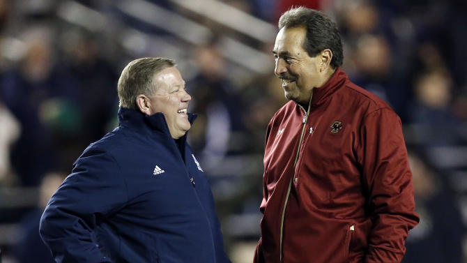 Notre Dame head coach Brian Kelly, left, talks with Boston College head coach Frank Spaziani before their NCAA college football game in Boston on Saturday, Nov. 10, 2012. (AP Photo/Winslow Townson)