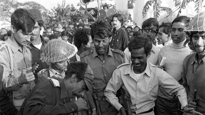 FILE - In this  Dec. 18, 1971 file photo shot by Associated Press photographers Horst Faas and Michel Laurent, part of a Pulitzer prize winning series, a guerilla leader in Dacca, Bangladesh, beats a victim during the torture and execution of four men suspected of collaborating with Pakistani militiamen accused of murder, rape and looting during months of civil war. Faas, a prize-winning combat photographer who carved out new standards for covering war with a camera and became one of the world's legendary photojournalists in nearly half a century with The Associated Press, died Thursday May 10, 2012. He was 79. (AP Photo/Horst Faas, Michel Laurent)