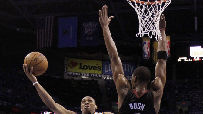 Oklahoma City Thunder point guard Russell Westbrook (0) shoots around Miami Heat power forward Chris Bosh during the first half at Game 2 of the NBA finals basketball series, Thursday, June 14, 2012, in Oklahoma City. (AP Photo/Jeff Roberson, Pool)