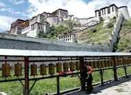 This file photo shows a Tibetan pilgrim spinning prayer wheels at the grounds of the Potala Palace in Lhasa, in 2003. Tibetans have long chafed under China's rule over the vast Tibetan plateau, accusing Beijing of curbing religious freedoms and eroding their culture and language