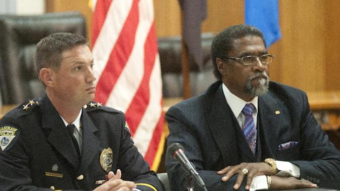 Acting Police Chief Brian Lipe, left, and city manager Darnell Earley listen during a press conference Friday, Sept. 21, 2012 at Saginaw City Hall, in Saginaw, Mich., announcing the results of the Administrative Review Task Force he appointed to review the shooting of Milton Hall that occurred on July 1, 2012 and the actions of the Saginaw police officers involved.  The on-scene supervisor during the July 1 shooting of Milton Hall, 49, was reprimanded and demoted to the rank of patrolman, Acting Police Chief Brian Lipe said, and the two officers being disciplined received reprimands for not following the department's mobile video and audio policy.    (AP Photo/Saginaw News, Jeff Schrier) LOCAL TV OUT; LOCAL INTERNET OUT