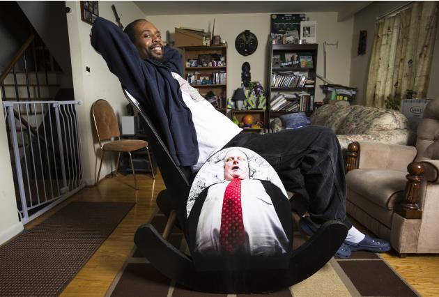 "Nuwame, poses on his ""Mayor Rob Ford Crack Rocker"", a rocking chair made completely of cardboard in Mississauga"