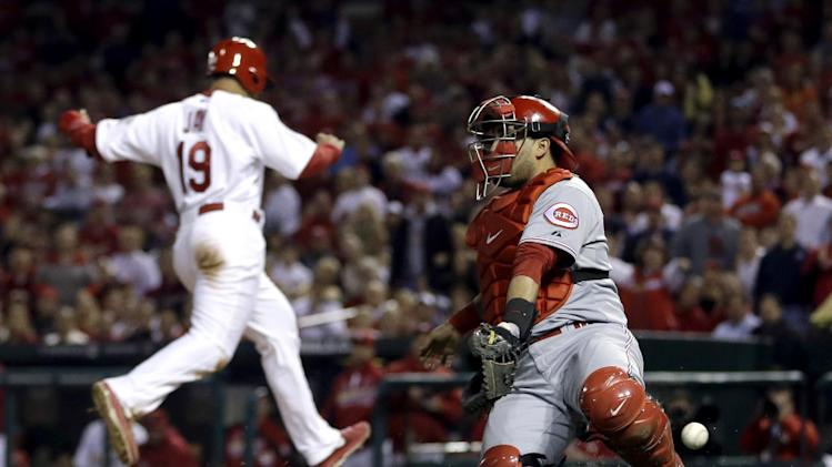St. Louis Cardinals' Jon Jay, left, scores on a sacrifice fly by Matt Holliday as Cincinnati Reds catcher Dioner Navarro reaches for the throw during the first inning of a baseball game, Tuesday, Oct. 2, 2012, in St. Louis. (AP Photo/Jeff Roberson)