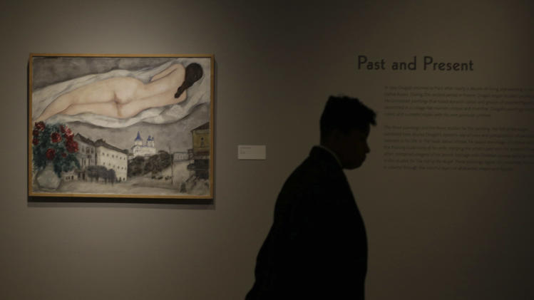 "In this photo taken Wednesday, Feb. 13, 2013, guard stands by the 1933 painting ""Nude Above Vitebsk,"" by artist Marc Chagall included in the ""Chagall: Beyond Color,"" exhibit during a preview at the Dallas Museum of Art Wednesday, Feb. 13, 2013, in Dallas. This will be the only U.S. venue to host the exhibit that opens to the public on Sunday. (AP Photo/LM Otero)"
