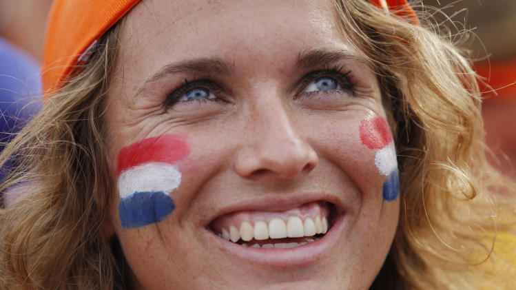 A Dutch soccer fans smiles while watching a live broadcast of the group B World Cup match between Chile and Netherlands, inside the FIFA Fan Fest area on Copacabana beach, in Rio de Janeiro, Brazil, Monday, June 23, 2014. Netherlands won 2-0, taking the top spot in group B. (AP Photo/Leo Correa)(AP Photo/Leo Correa)
