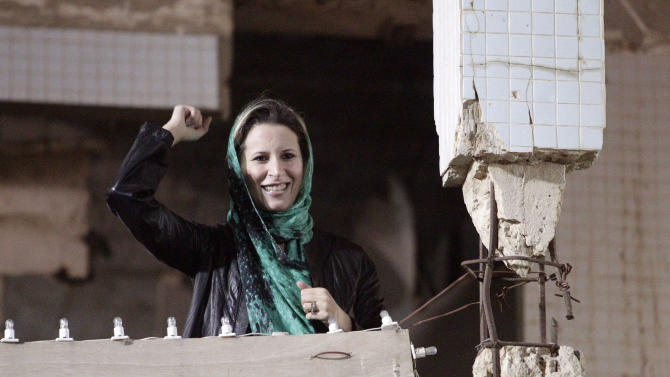 Aisha Gadhafi, daughter of Libyan leader Moammar Gadhafi, waves as she addresses Libyan people gathering at the Bab Al Azizia compound in Tripoli, Libya, early Friday, April 15, 2011.  (AP Photo/Pier Paolo Cito)