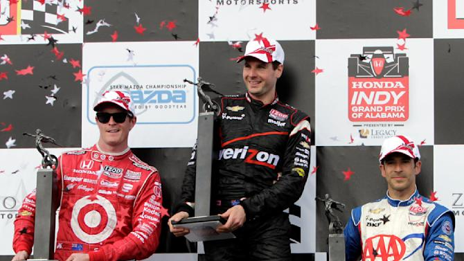 Will Power, center, of Australia, holds the trophy after he won the IndyCar Series' Indy Grand Prix of Alabama auto race, as second-place finisher Scott Dixon, left, of New Zealand, and third-place Helio Castroneves, of Brazil, join him on the podium Sunday, April 1, 2012, in Birmingham, Ala. (AP Photo/Butch Dill)