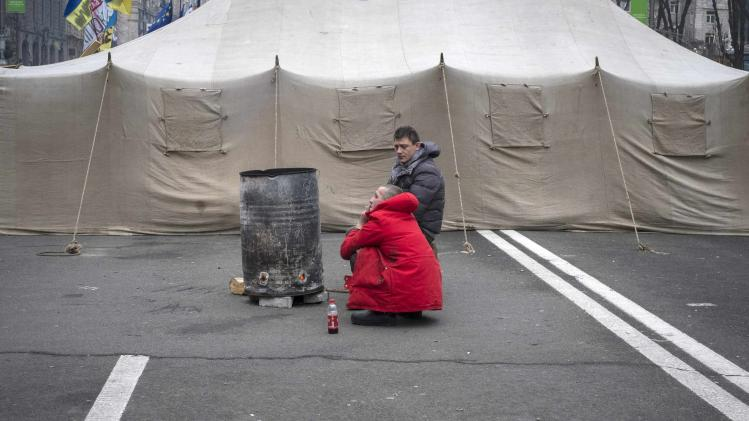 Ukrainian pro-EU demonstrators warm themselves near a fire burning in a steel drum during a rally in Independence Square in central Kiev