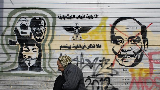 """An elderly Egyptian woman walks past a mural depicting military ruler Field Marshal Hussein Tantawi with Arabic that reads """"If you see the teeth, don't think that the lion is smiling"""" at Tahrir Square in Cairo, Egypt Thursday, Feb. 23, 2012. (AP Photo/Nasser Nasser)"""