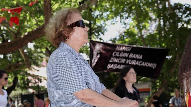 "Demonstrators stand in a silent protest in Kugulu Park in Ankara, Turkey, Wednesday, June 19, 2013. After weeks of sometimes-violent confrontation with police, Turkish protesters have found a new form of resistance: standing still and silent. The banner with an image of Turkey's founder Kemal Ataturk reads: ""Which crazy person thinks they can put me in chains."" (AP Photo/Burhan Ozbilici)"