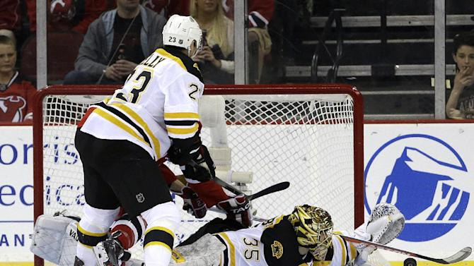Boston Bruins goalie Anton Khudobin (35), of Kazakhstan, deflects a shot as center Chris Kelly, left, defends against New Jersey Devils center David Clarkson, back, during the first period of an NHL hockey game, Wednesday, April 10, 2013, in Newark, N.J. (AP Photo/Julio Cortez)