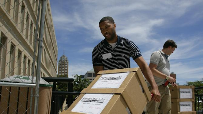 Micheal Davis, left, and Eric Keller, volunteers with the Protect Our Jobs Coalition, deliver boxes of petitions for a proposal to add collective bargaining rights for workers into the Michigan Constitution to the state Bureau of Elections Wednesday, June 13, 2012, in Lansing, Mich. The Protect Our Jobs initiative was launched in March. It pushes back against a possible right-to-work movement in Michigan, which seeks to ban labor contracts that mandate payments to unions. (AP Photo/Al Goldis)