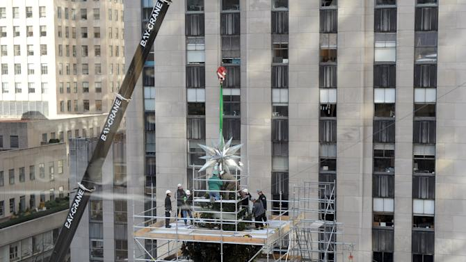 IMAGE DISTRIBUTED FOR SWAROVSKI - The 2012 Swarovski Star is placed atop the Rockefeller Center Christmas Tree, Tuesday, Nov. 20, 2012, in New York, and features 25,000 crystals and weighs 550 pounds.  Swarovski is the leading designer and producer of fashion jewelry and crystal decor objects.   (Diane Bondareff/Invision for Swarovski/AP Images)