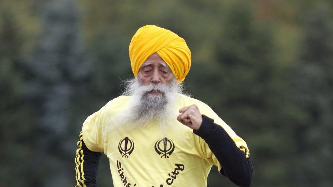 Centenarian Fauja Singh crosses the finish line in a 100 meter race for centenarians in Toronto,  Thursday Oct. 13, 2011.  One-hundred-year-old Singh, originally from India now living in London,  England, is competing in Toronto's Waterfront Marathon on Sunday. (AP Photo/The Canadian Press, Chris Young)