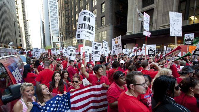 Thousands of public school teachers rally outside the Chicago Public Schools district headquarters on the first day of strike action over teachers' contracts on Monday, Sept. 10, 2012 in Chicago. For the first time in a quarter century, Chicago teachers walked out of the classroom Monday, taking a bitter contract dispute over evaluations and job security to the streets of the nation's third-largest city — and to a national audience — less than a week after most schools opened for fall.  (AP Photo/Sitthixay Ditthavong)