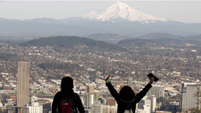 """FILE - In this file photo from Feb. 26, 2008, a young couple enjoys the view of Mount Hood looming over downtown on a spring-like day in Portland, Ore. A famous quip by Fred Armisen on the television show """"Portlandia"""" led Portland State University researchers to investigate the reality behind the comment. The quirky IFC network series pokes fun at the Oregon city's many eccentricities. (AP Photo/Don Ryan, File)"""