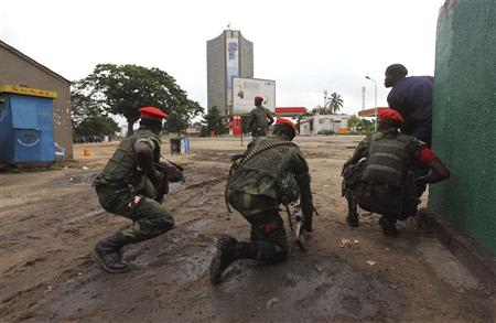Congolese security officers position themselves as they secure the street near the state television headquarters (C) in the capital Kinshasa.