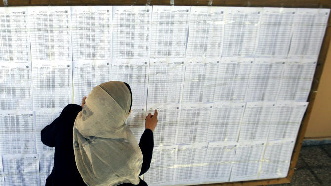 A Palestinian woman points at a voters list ahead of the upcoming elections, in Gaza City,  Monday, Feb. 11, 2013. The Palestinian election commission has started to update voter registers in the West Bank and Gaza Strip to pave the way for new elections — and possible reconciliation between the rival Fatah and Hamas factions. (AP Photo/Hatem Moussa