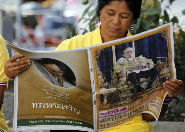 Anti-government protester reads a newspaper with a picture of Thailand's King Bhumibol delivering his birthday speech during a rally at Thailand's Finance Ministry in central Bangkok