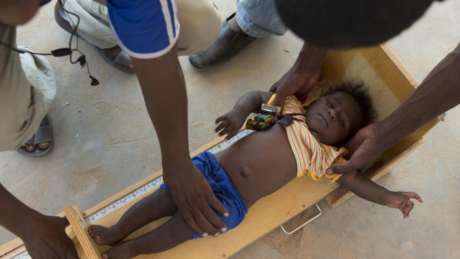 In this Nov. 4, 2012 photo, health workers measure the height of a boy during a mobile clinic to identify cases of underweight, stunted, or malnourished children, in Michemire, in the Mao region of Chad. A survey conducted in the county found that 51.9 percent of the children are stunted, one of the highest rates in the world, according to a summary published by UNICEF. Stunting is the result of having either too few calories, too little variety, or both. (AP Photo/Rebecca Blackwell)