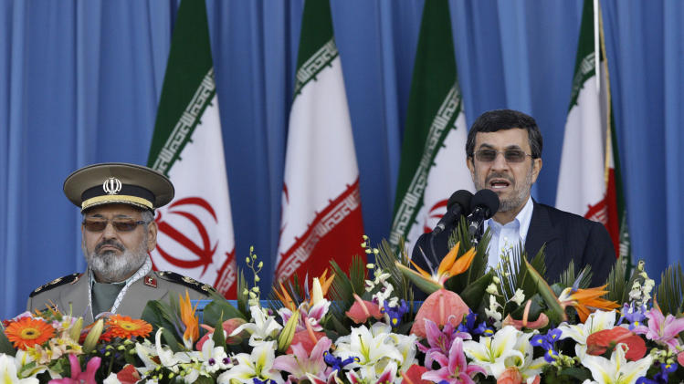 Iranian President Mahmoud Ahmadinejad, right, speaks, as Chief of the General Staff of Iran's Armed Forces, Gen. Hasan Firouzabadi, listens, during army parade commemorating National Army Day in front of the mausoleum of the late revolutionary founder Ayatollah Khomeini, outside Tehran, Iran, Tuesday, April 17, 2012. Iran's president said that the country's armed forces will make its enemy's regret any act of aggression against Iran. (AP Photo/Vahid Salemi)